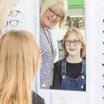 Photo of a blonde lady and a young girl looking into a mirror in an opticians