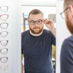 Photo of a man with a dark hair and a beard looking into a mirror in an opticians