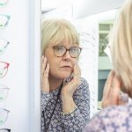 Photo of a blonde lady wearing glasses looking into a mirror in a opticians
