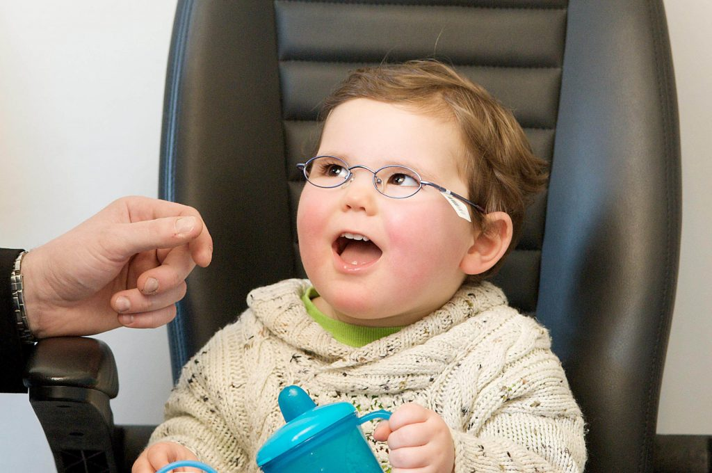 A toddler aged boy sits in a chair at the opticians wearing glasses