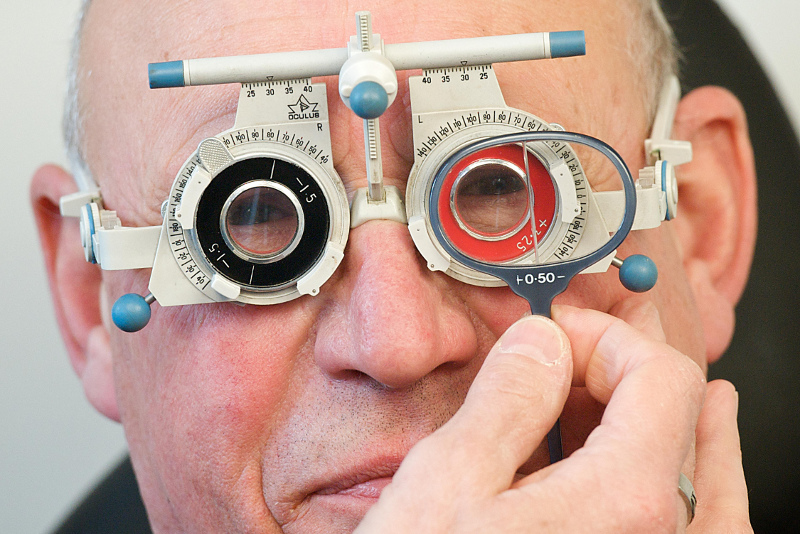 A man wearing opticians eye testing frames during an eye test appointment